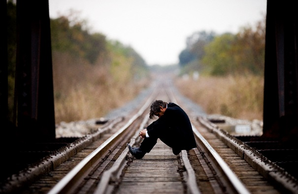 Man Sitting on a Railroad Bridge