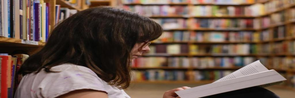 Mulher sentada em livraria lendo um livro.