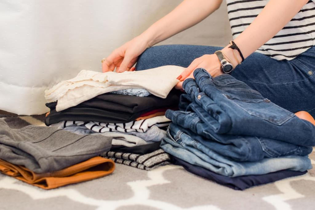 Mulher organizando uma  pilha de roupas.
