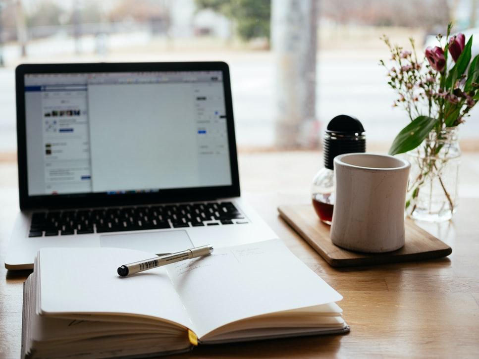 Mesa preparada para escrever, com Notebook, caderno e uma xícara de café.