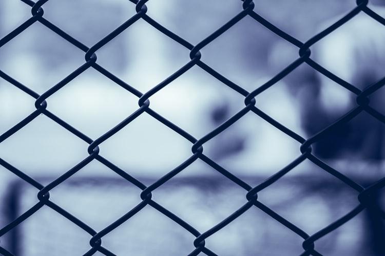 Confinada, olhando por janela fechada com grades.
