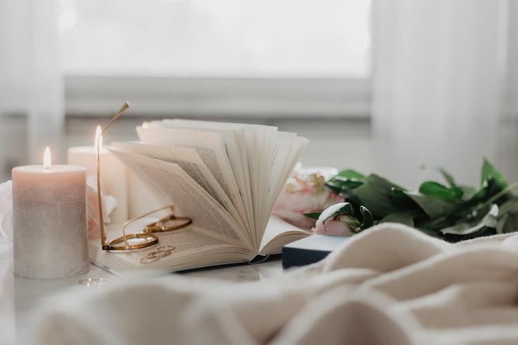 Foto com livro e vela acesa, em um espaço bastante confortável para um ritual de autocuidado.