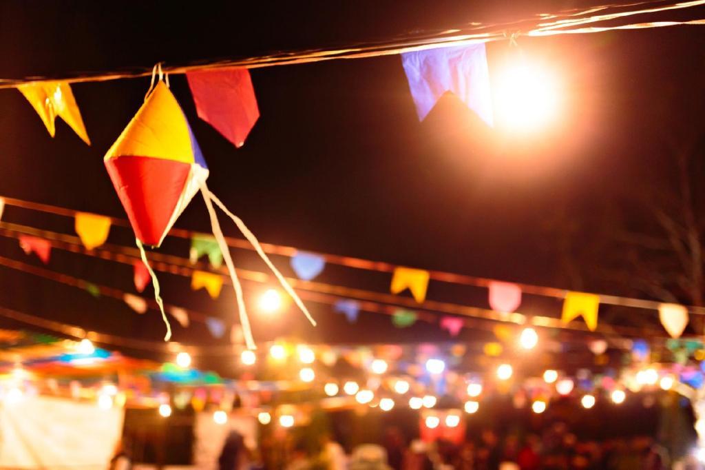 Imagem de festa junina, é noite e há luzes e bandeirinhas espalhadas pela rua.