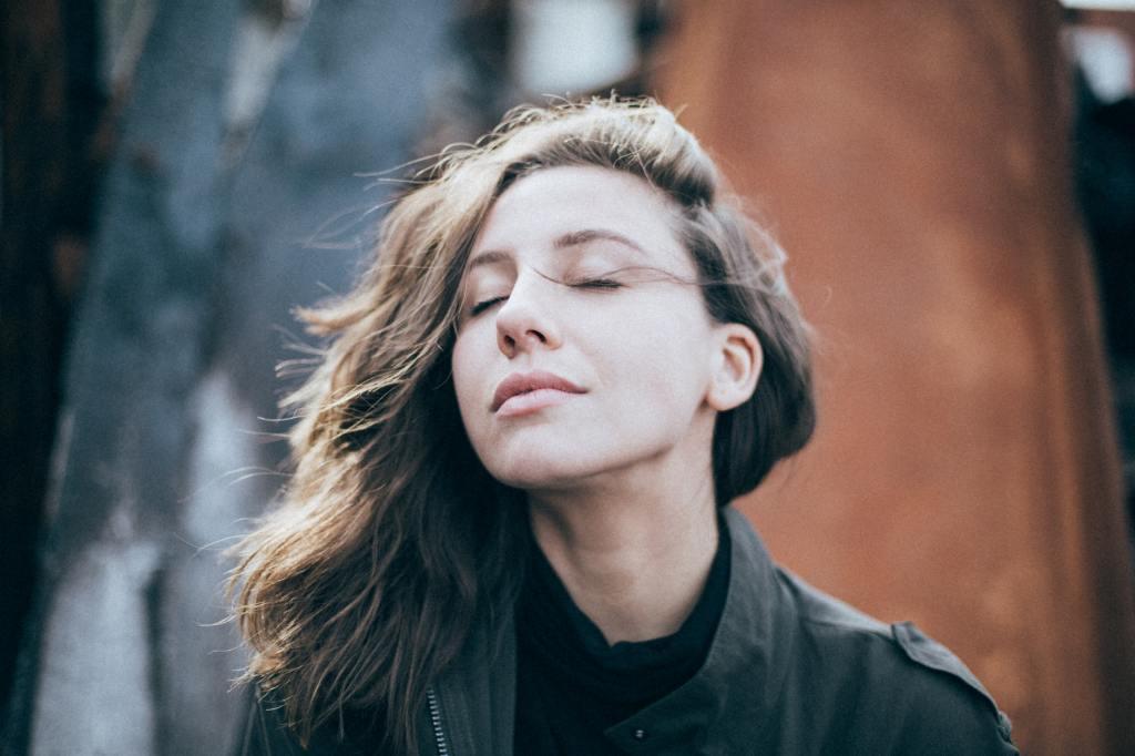 Mulher de olhos fechados, inspirando calmamente.