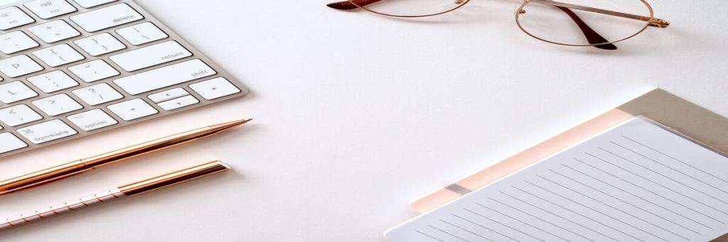 Mesa organizada com caderno e laptop, para discutir a forma de nomear arquivos.